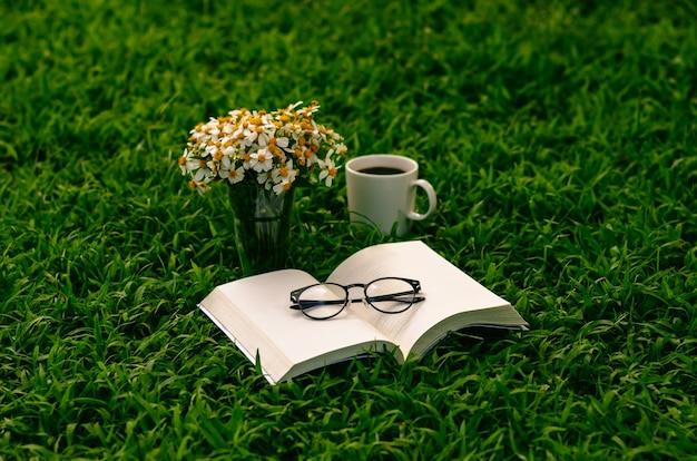Loisirs le matin au jardin avec café, livre et fleurs sur la pelouse.
