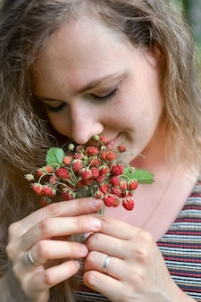 Loisirs de plein air la jeune fille apprécie l'arôme des fraises fraîchement cueillies dans la forêt