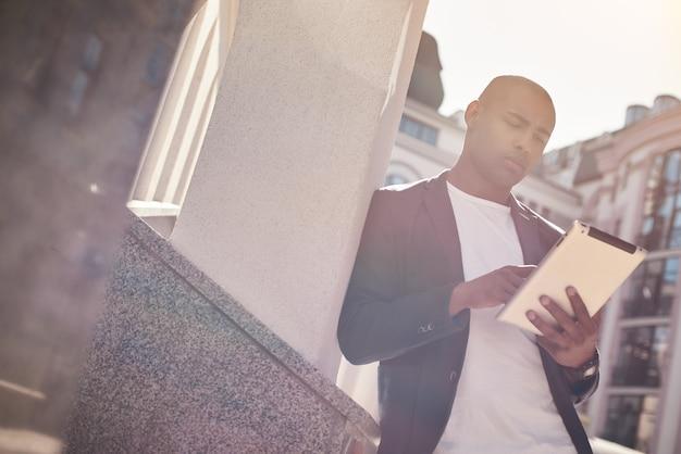Loisirs de plein air jeune homme debout dans la rue de la ville s'appuyant sur un mur en naviguant sur internet