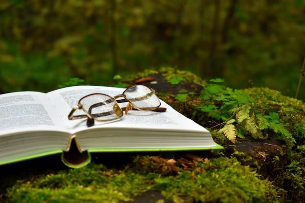Loisirs pour les seniors. livre et verres sur une souche dans le parc. lecture pour les personnes âgées.