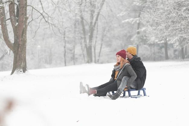 Long coup de couple jouant avec traîneau dans la neige