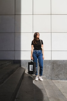 Long mode femme posant avec un sac à provisions