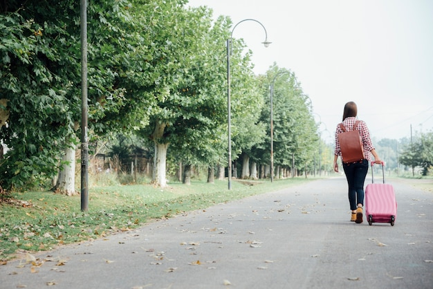 Long plan de la femme avec ses bagages