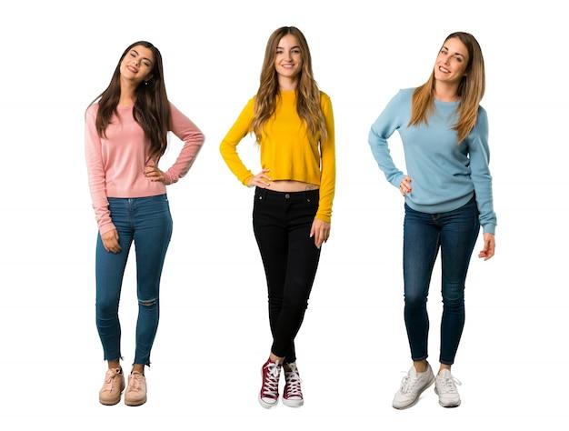 Un long plan d'un groupe de personnes avec des vêtements colorés qui posent avec les bras à la hanche et souriant