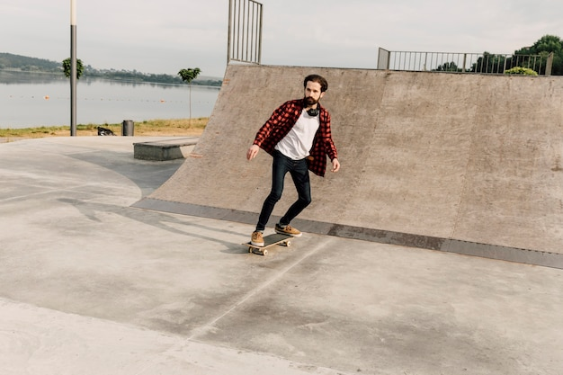Long plan de l'homme au skate park