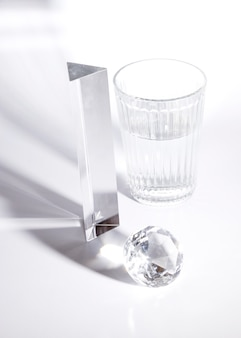 Long prisme; diamant et verre d'eau au soleil avec ombre sur fond blanc