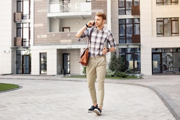 Le long de la rue. agréable bel homme parlant au téléphone en marchant le long de la rue
