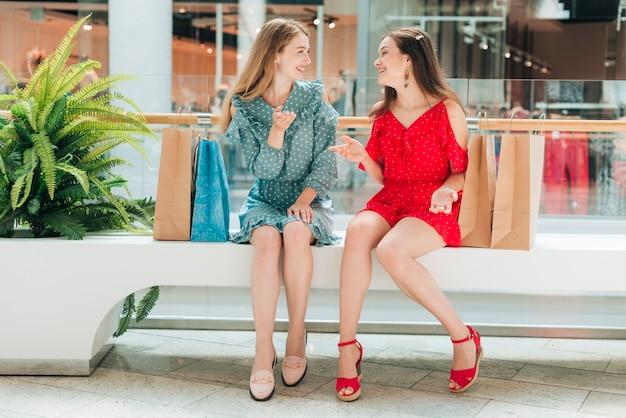 Long shot amis discutant au centre commercial