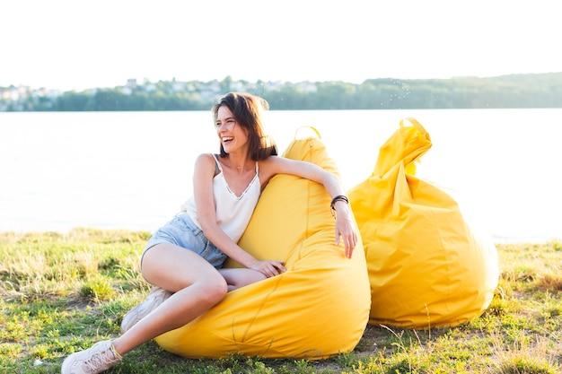 Long shot belle femme posant sur un pouf jaune