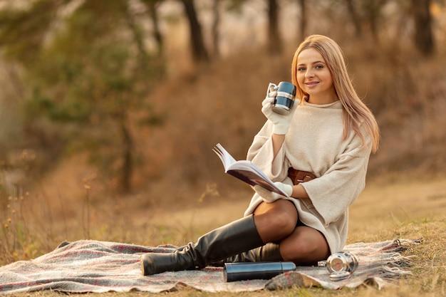 Long shot blonde femme lisant un livre