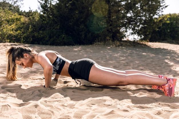 Long shot côté vue femme faisant des push ups