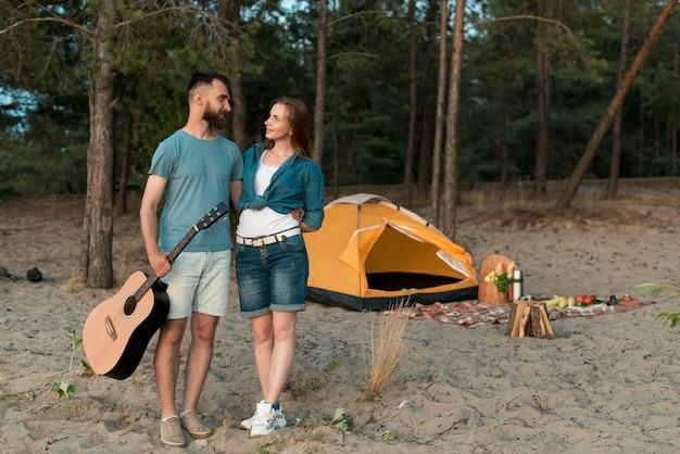 Long shot couple debout à côté de la tente