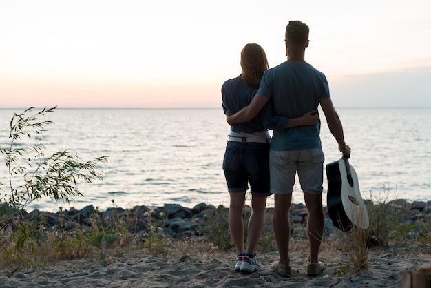 Long shot couple debout près de l'eau