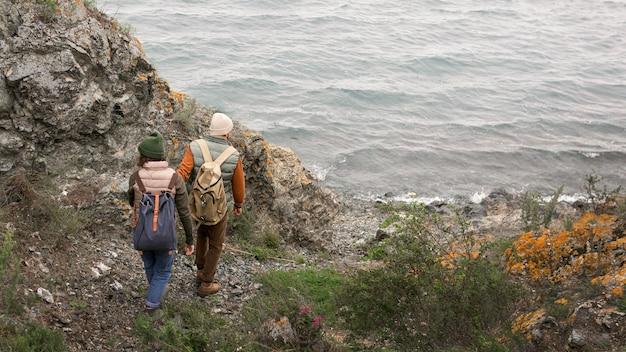 Long shot couple marchant vers la mer