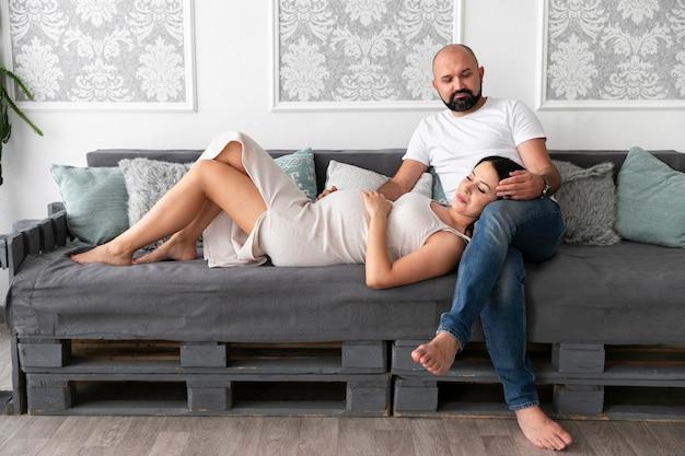 Long shot couple relaxant sur le canapé