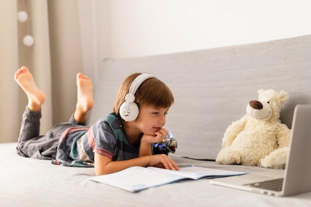 Long shot enfant fréquentant des cours d'école virtuelle