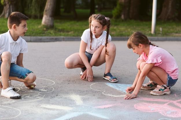 Long shot enfants dessinant à la craie