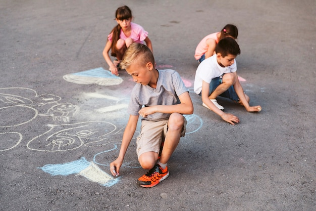 Long shot enfants faisant un dessin à la craie