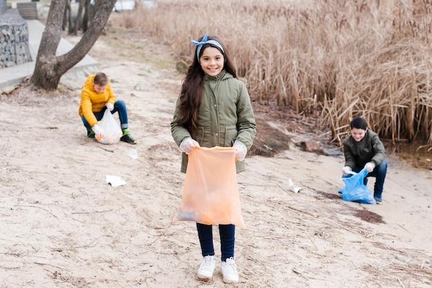 Long shot sur les enfants avec des sacs en plastique