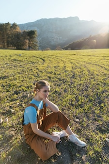 Long shot femme assise sur l'herbe