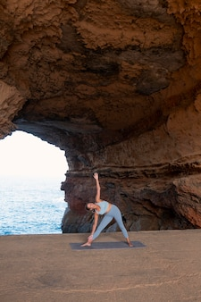 Long shot femme faisant du yoga pose