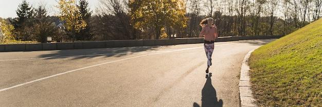 Long shot femme jogging dans le parc