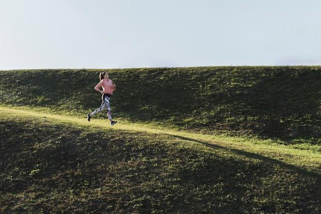 Long shot femme qui court dans le parc