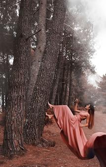 Long shot femme en robe grimper à un arbre
