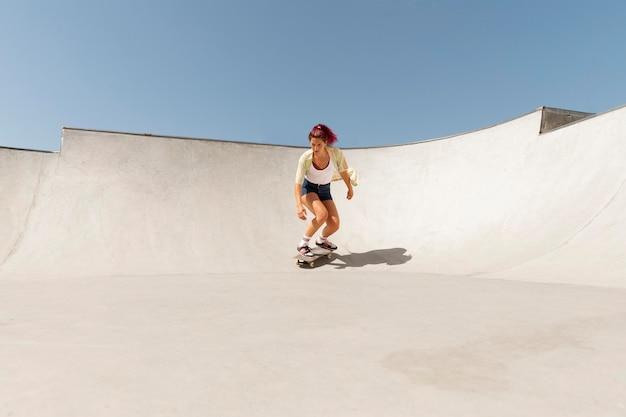 Long shot femme sur skateboard
