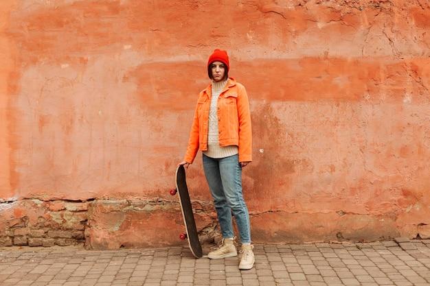 Long shot femme tenant une planche à roulettes en bois
