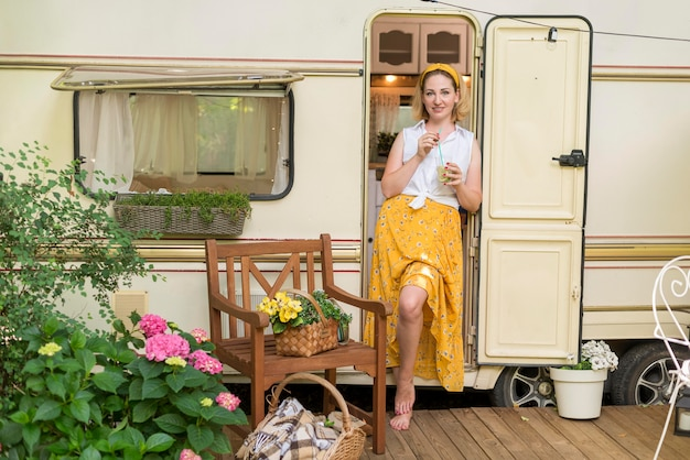 Long shot femme tenant un verre de limonade à côté d'une caravane