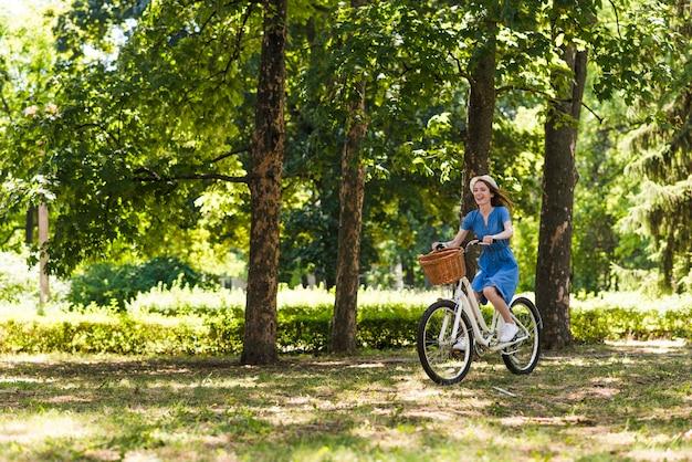Long shot femme à vélo en forêt