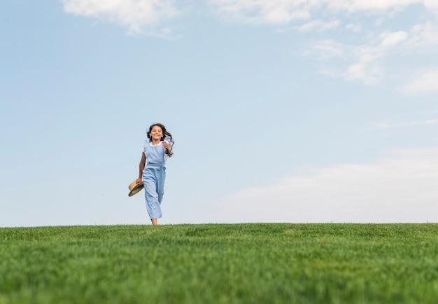 Long shot fille aux cheveux longs en cours d'exécution sur l'herbe