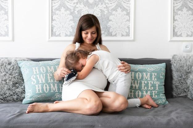 Long shot fille embrassant sa mère sur le canapé