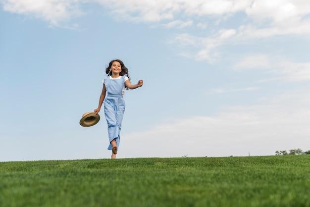 Long shot fille marchant pieds nus sur l'herbe