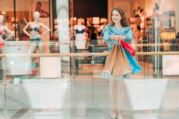 Long shot fille en robe au centre commercial