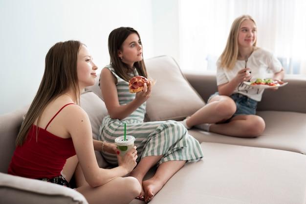 Long shot filles en train de manger une pizza sur un canapé