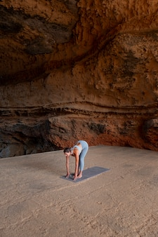 Long shot fit woman doing yoga en plein air
