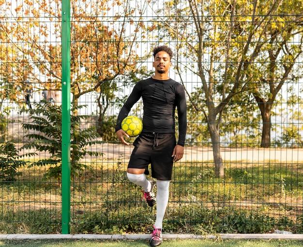Long shot homme afro-américain posant avec un ballon de foot