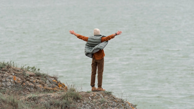 Long shot homme avec les mains en l'air face à l'eau