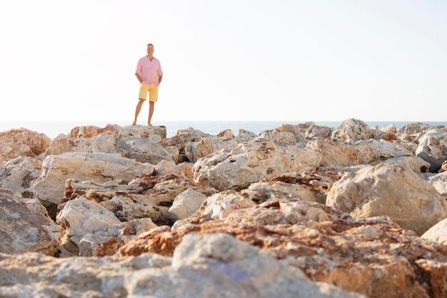 Long shot homme posant sur des rochers