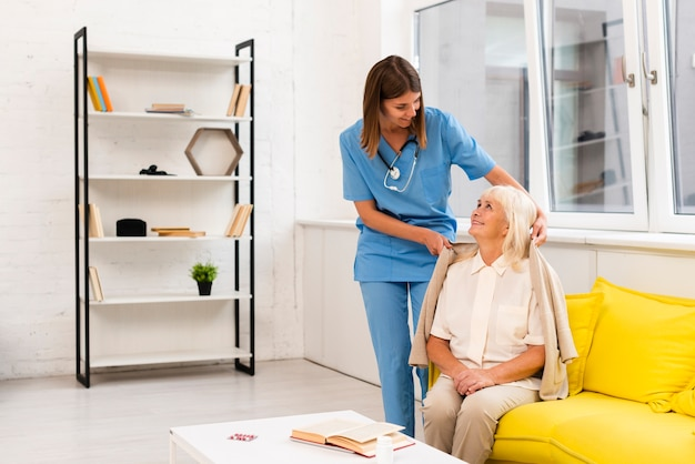 Long shot infirmière aidant vieille femme avec son manteau