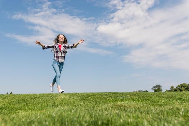 Long shot jolie fille en cours d'exécution sur l'herbe