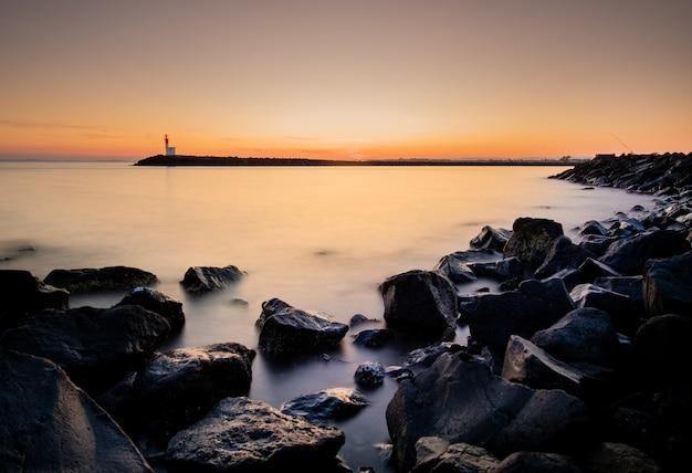 Long shot magnifique coucher de soleil sur un port brumeux