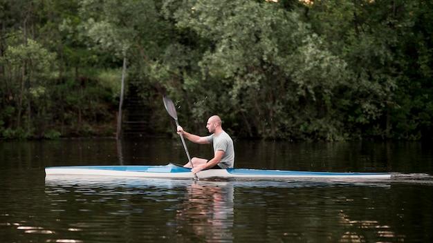 Long shot man en kayak avec pagaie