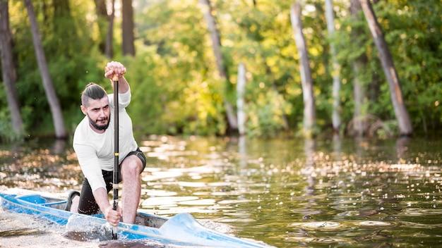 Long shot man paddling