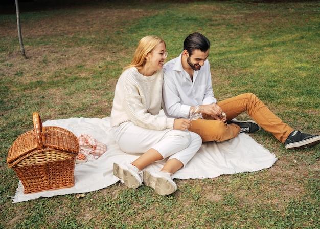 Long shot mari et femme ayant un pique-nique ensemble à l'extérieur