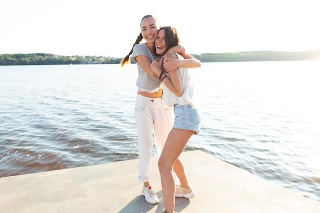 Long shot meilleurs amis embrassant sur le quai