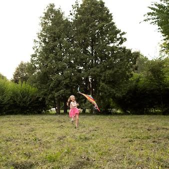 Long shot of happy girl s'amuser avec un cerf-volant