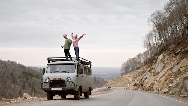 Long shot personnes debout sur van